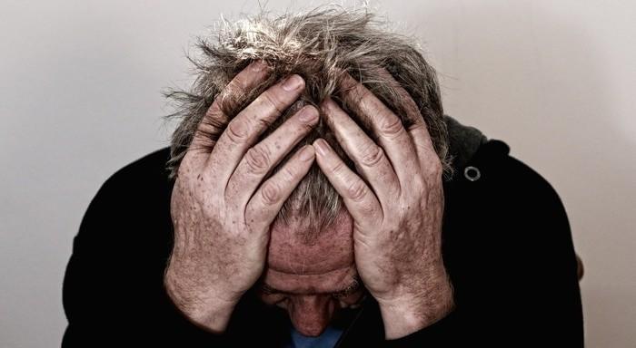 Schmerzgeplagter Mann, der die Hände über dem Kopf zusammenschlägt.
