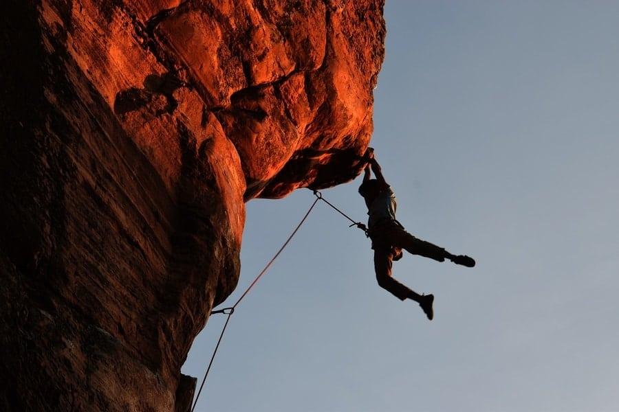 Kletterer auf roter Felswand.